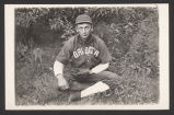 Man in baseball uniform sitting